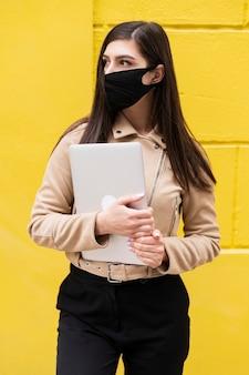 ラップトップを保持しているフェイスマスクを持つ女性の正面図