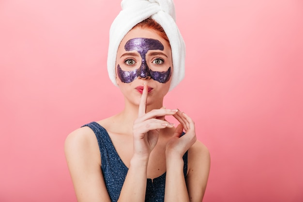 Вид спереди женщины с лицевой маской, показывая знак тишины. студия выстрел молодой леди в полотенце, позирует на розовом фоне во время ухода за кожей.