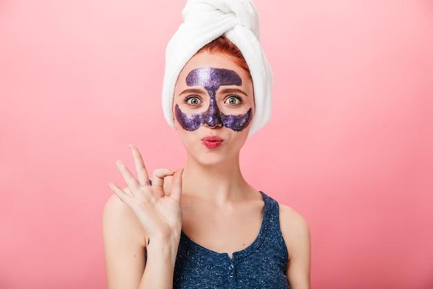 Вид спереди женщины с лицевой маской, показывая хорошо знаком. студия выстрел изумленной девушки с полотенцем на голове показывать на розовом фоне.