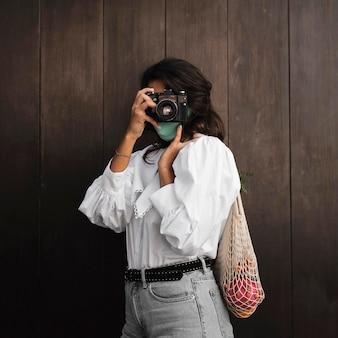 カメラで写真を撮るフェイスマスクを持つ女性の正面図