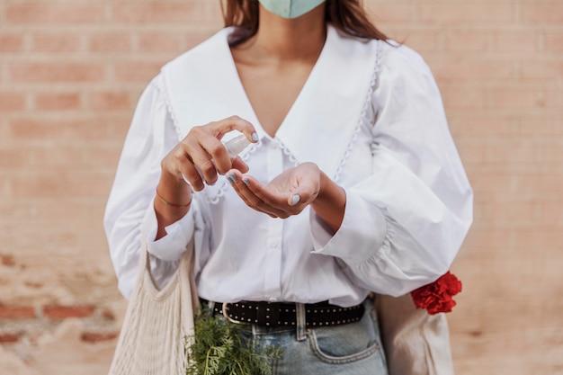 Вид спереди женщины с маской для лица, использующей дезинфицирующее средство для рук