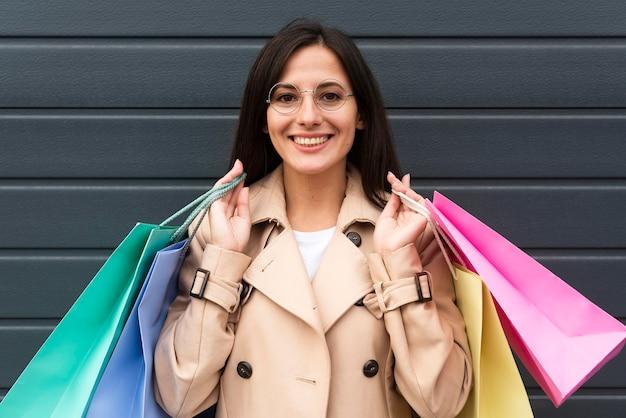 Вид спереди женщины в очках, держащей много сумок
