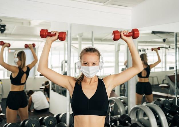 Вид спереди женщины с наушниками и медицинских тренировок в тренажерном зале