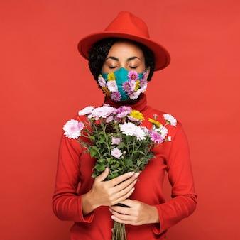 Вид спереди женщины с маской, держащей цветы
