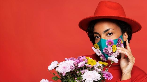 Вид спереди женщины с маской, позирующей с цветами