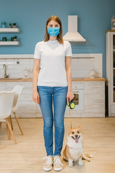 医療用マスクを持つ女性と綱の彼女の犬の正面図