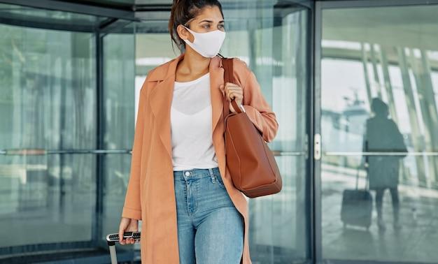 Вид спереди женщины с медицинской маской, несущей багаж в аэропорту во время пандемии