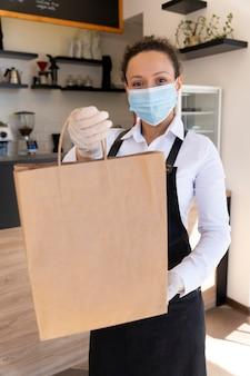 持ち帰り用食品と紙袋を保持している医療マスクを持つ女性の正面図 Premium写真