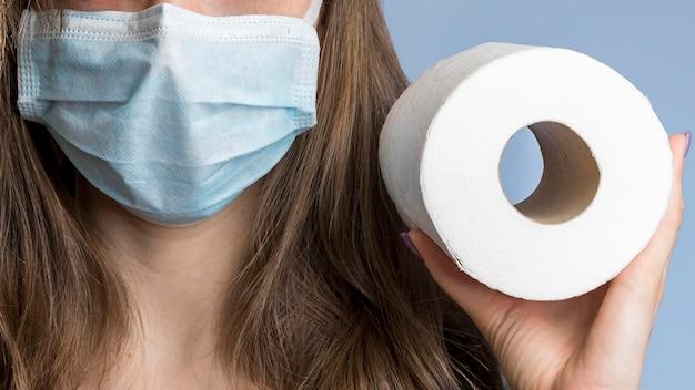 Вид спереди женщины с медицинской маской, держащей туалетную бумагу