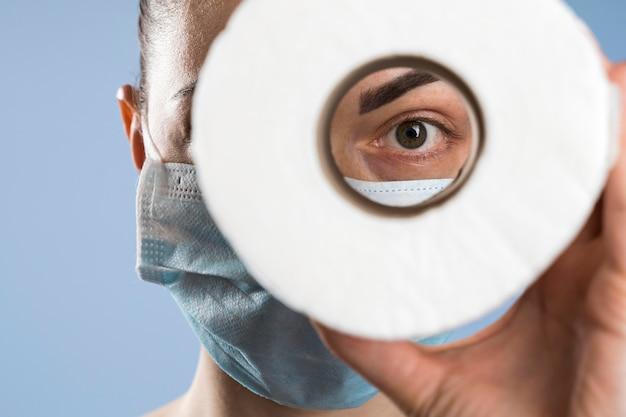 Вид спереди женщины с медицинской маской, глядя через туалетную бумагу