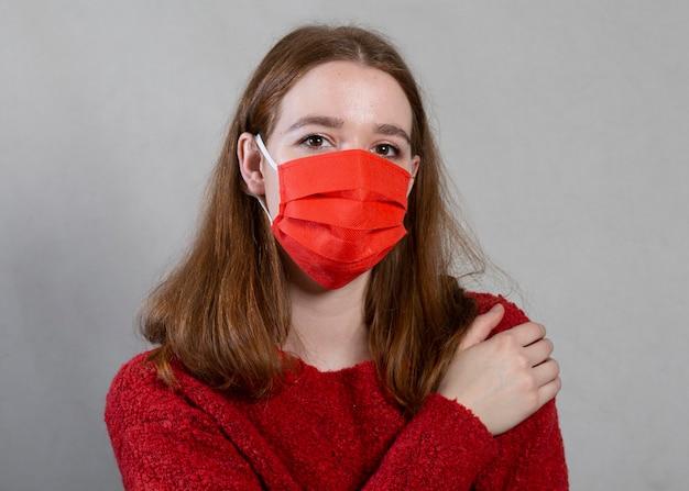 顔に医療マスクを持つ女性の正面図