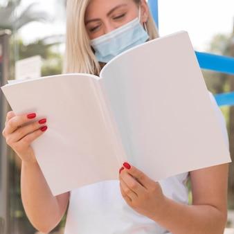 外で本を読んで医療マスクを持つ女性の正面図