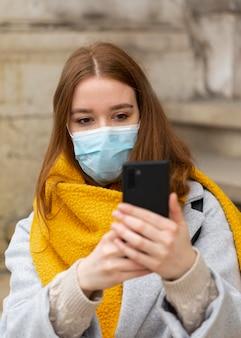 スマートフォンで写真を撮る医療マスクを持つ女性の正面図