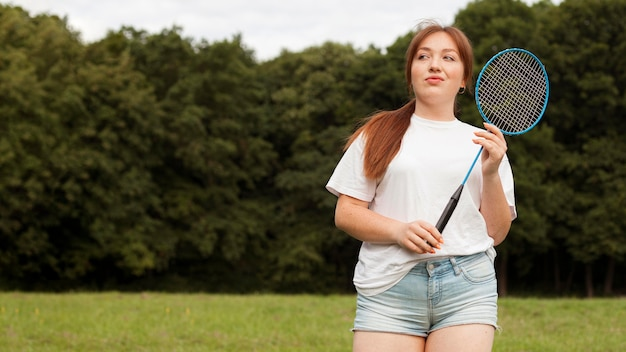 Вид спереди женщины с ракеткой на открытом воздухе