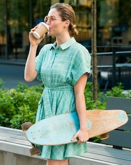 Вид спереди женщины с скейтбордом