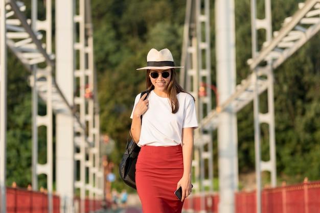 Вид спереди женщины в солнцезащитных очках и шляпе, путешествующей в одиночку