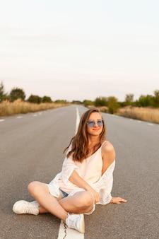 Вид спереди женщины в солнцезащитных очках, позирующей на дороге