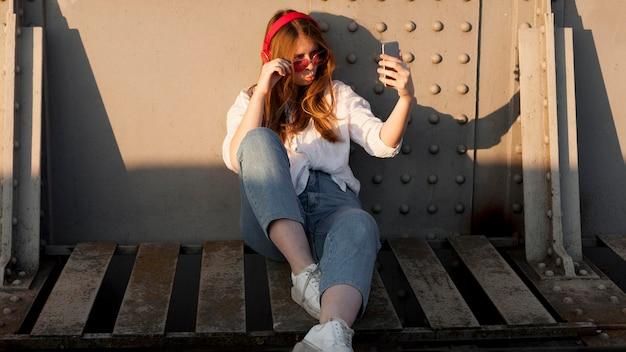 Вид спереди женщины с солнцезащитные очки, принимая селфи