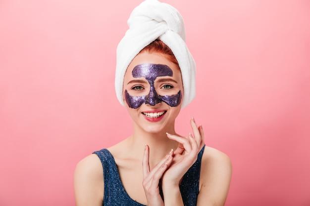 수건 및 얼굴 마스크를 가진 여자의 전면 모습. 분홍색 배경에 고립 된 스킨 케어 루틴을 하 고 웃는 소녀.