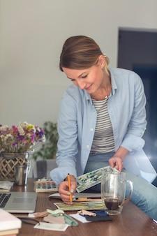 マグカップと机の上で働く女性の正面図