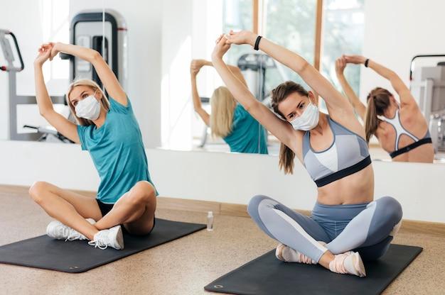 Вид спереди женщин, тренирующихся в тренажерном зале во время пандемии