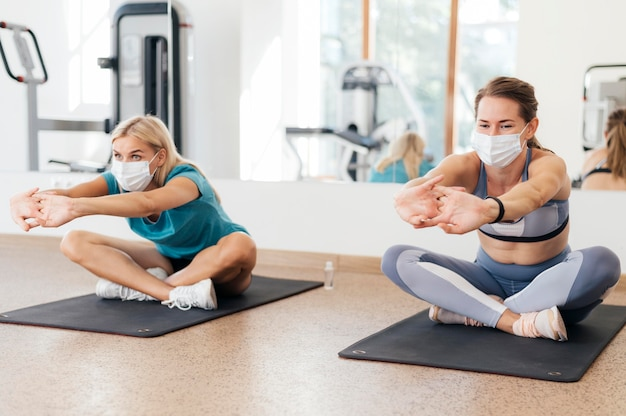 Вид спереди женщин, вместе тренирующихся в тренажерном зале во время пандемии