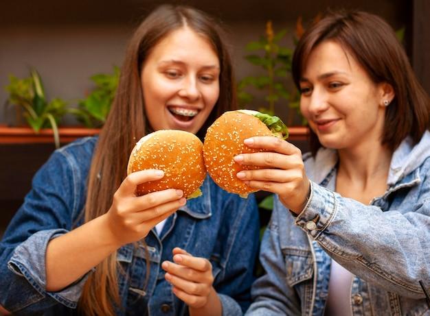 ハンバーガーで乾杯する女性の正面図