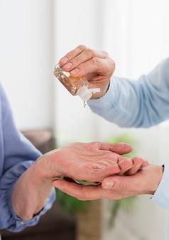 Вид спереди женщин, используя дезинфицирующее средство для рук
