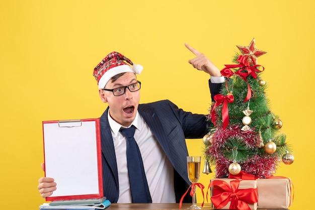 Вид спереди удивленного делового человека, сидящего за столом возле рождественской елки и подарков на желтом