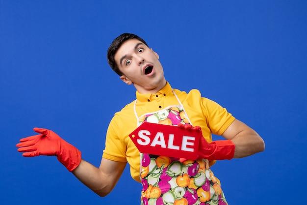 파란색 벽에 판매 표지판을 들고 있는 노란색 티셔츠를 입은 경이로운 남성 가정부의 전면