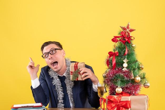 Вид спереди удивленного человека, держащего подарок, сидящего за столом возле рождественской елки и подарков на желтом