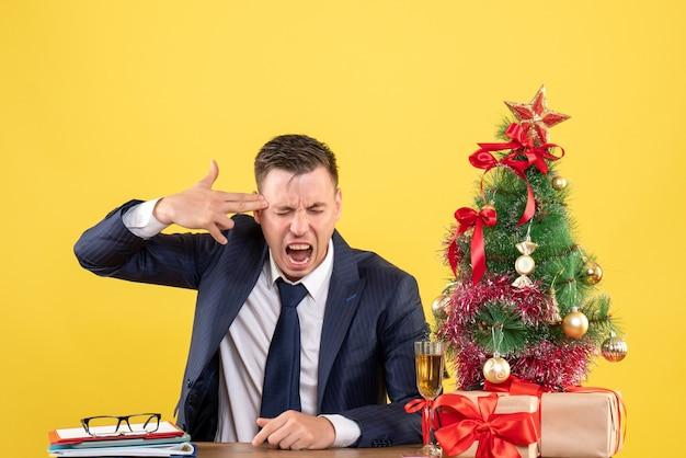 クリスマスツリーの近くのテーブルに座っている寺院に指銃を保持し、黄色で提示する不思議な男の正面図