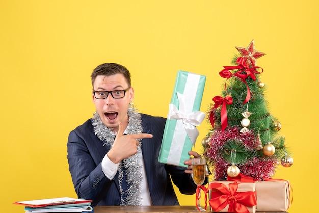 Вид спереди удивленного человека, указывающего на подарок, сидящего за столом возле рождественской елки и подарков на желтом