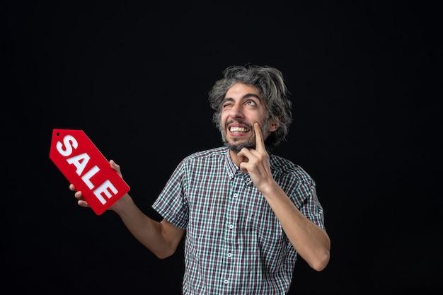 暗い壁に赤い販売サインを掲げているアイデアに驚いた不思議な男の正面図