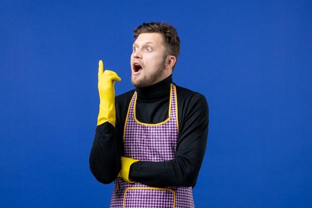 Вид спереди удивленного молодого мужчины, стоящего на синей стене