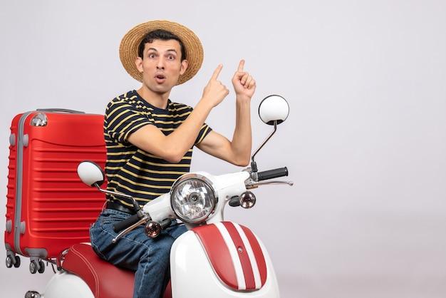 뒤에 가리키는 오토바이에 밀짚 모자와 궁금해 젊은 남자의 전면보기