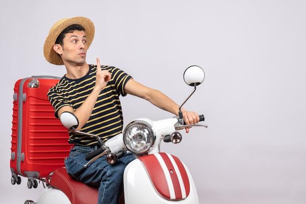 오토바이에 밀 짚 모자와 궁금해 젊은 남자의 전면보기