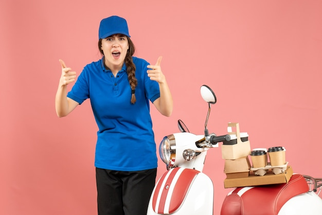 パステル ピーチ色の背景にコーヒーと小さなケーキを乗せたバイクの隣に立っている不思議な宅配便の女性の正面図