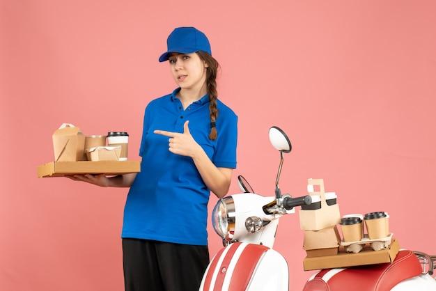 パステル ピーチ色の背景にコーヒーと小さなケーキを保持しているオートバイの隣に立っている不思議な宅配便の女性の正面図