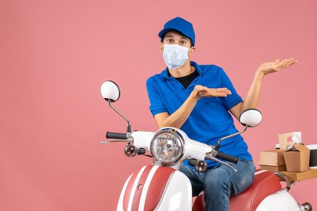 パステル調の桃の背景にスクーターに座っている帽子をかぶった医療マスクを着た不思議な宅配便の男性の正面図