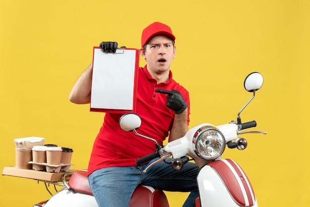 文書を保持しているスクーターに座って注文を配信する医療マスクで赤いブラウスと帽子の手袋を身に着けている不思議な宅配便の男の正面図