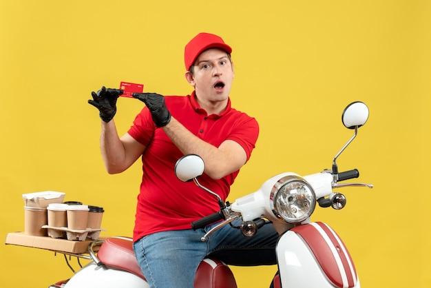 銀行カードを示すスクーターに座って注文を配信する医療マスクで赤いブラウスと帽子の手袋を身に着けている不思議な宅配便の男の正面図