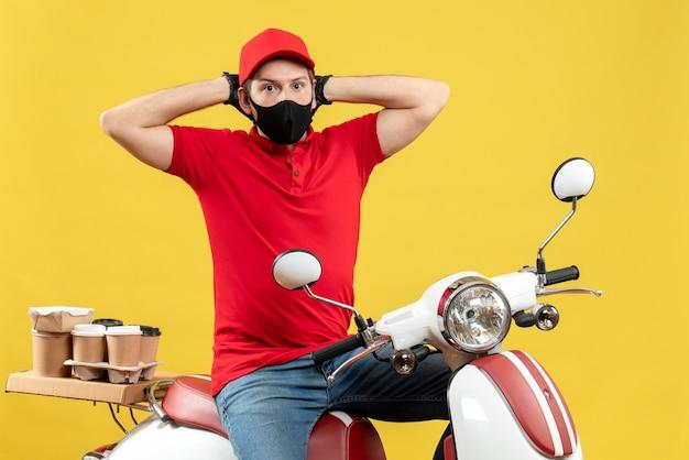 医療用マスクに赤いブラウスと帽子の手袋を着用してスクーターに座って注文を配信する不思議な宅配便の男の正面図