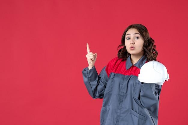 Вид спереди удивленной женщины-архитектора, держащей каску и указывающей вверх на изолированном красном фоне