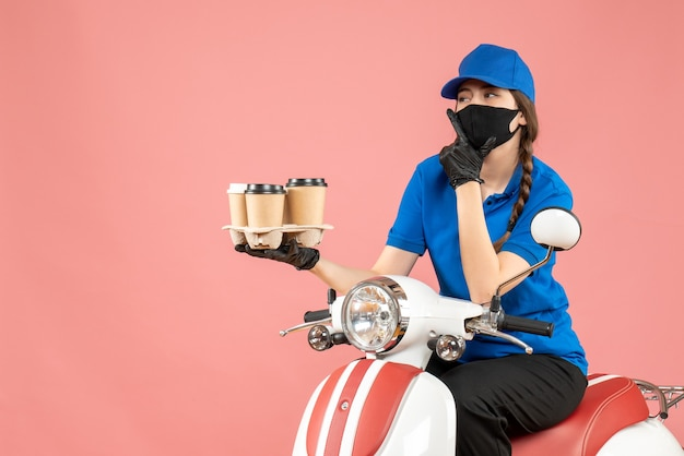 パステルピーチの背景に注文を保持しているスクーターに座っている医療用マスクと手袋を身に着けている疑問に思っている女性の配達員の正面図