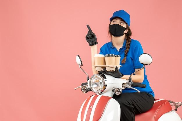 医療用マスクと手袋を着て、パステル調の桃の背景に注文を保持しているスクーターに座っている女性の配達員の正面図