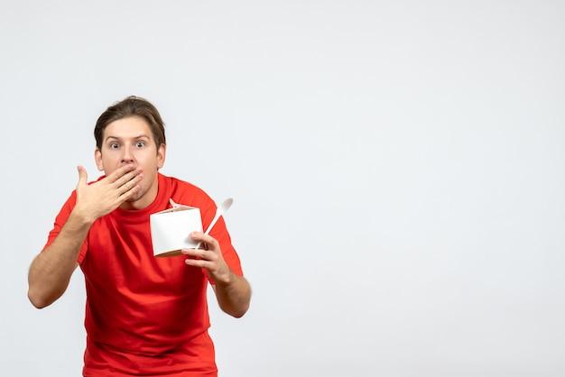 白い背景の上の紙箱とスプーンを保持している赤いブラウスの不思議な若い男の正面図