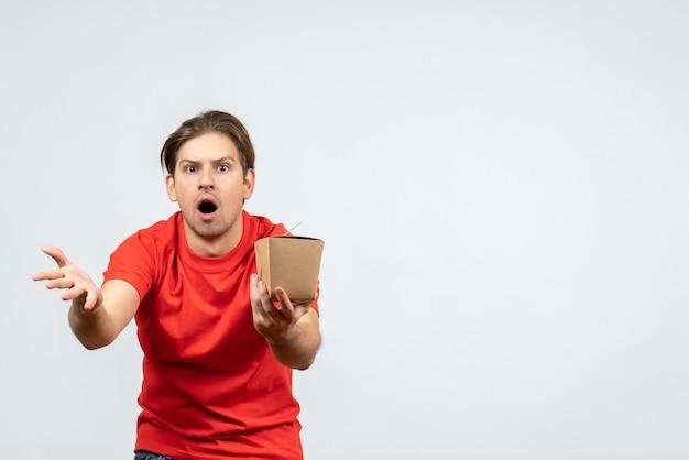 Вид спереди удивленного молодого парня в красной блузке, держащего коробочку на белом фоне