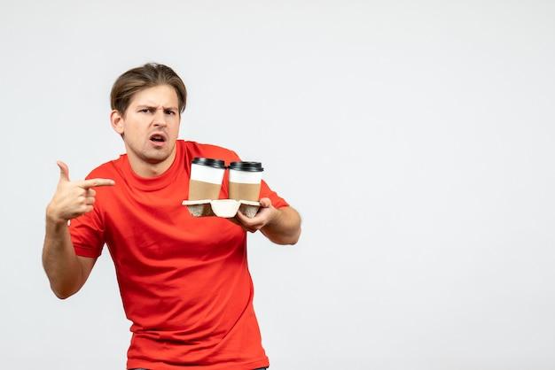 白い背景の上の紙コップでコーヒーを指す赤いブラウスの不思議な若い男の正面図