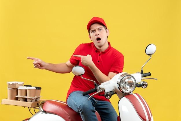 黄色の背景の右側に何かを指している注文を配信する赤いブラウスと帽子を身に着けている不思議な若い男の正面図